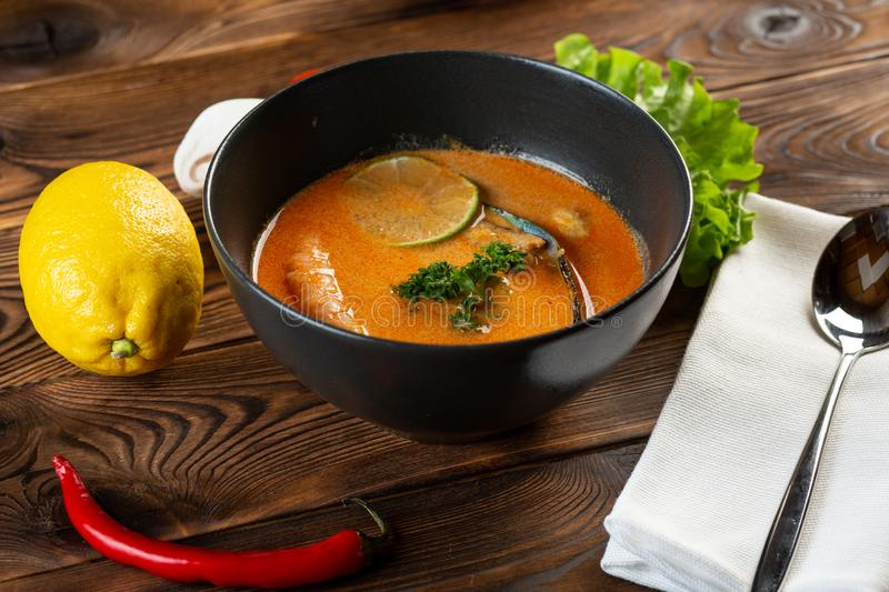 Soup tom yam in a black plate on a wooden background royalty free stock image