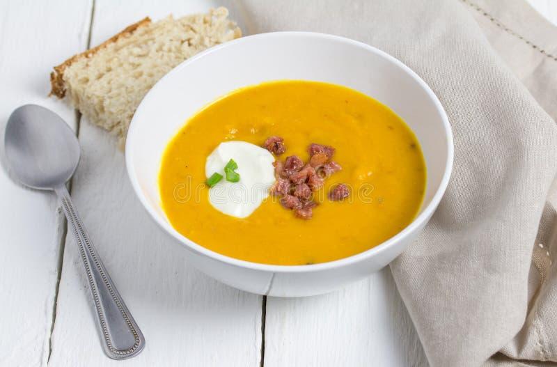 Soupe à Butternut et à lard avec la crème sure, le peu de lard et le scallio photographie stock