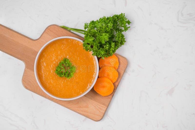 Soupe à carotte avec de la crème et le persil sur le fond en pierre blanc À photographie stock libre de droits