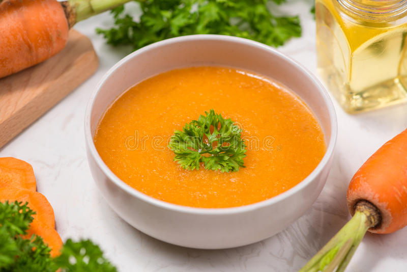 Soupe à carotte avec de la crème et le persil sur le fond en pierre blanc À photos stock