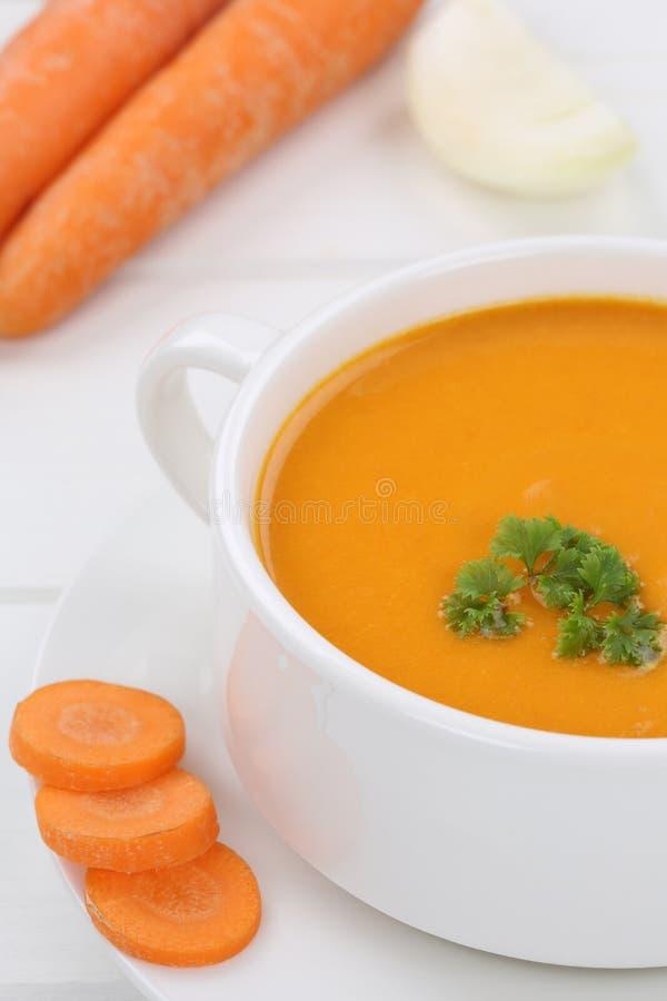 Soupe à carotte avec les carottes fraîches en plan rapproché de cuvette photographie stock