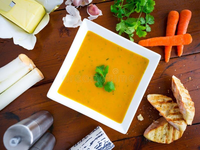 Soupe à carotte et à coriandre avec des ingrédients photographie stock