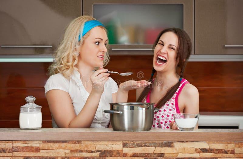 Soupe à essai de jeunes filles dans la cuisine images libres de droits
