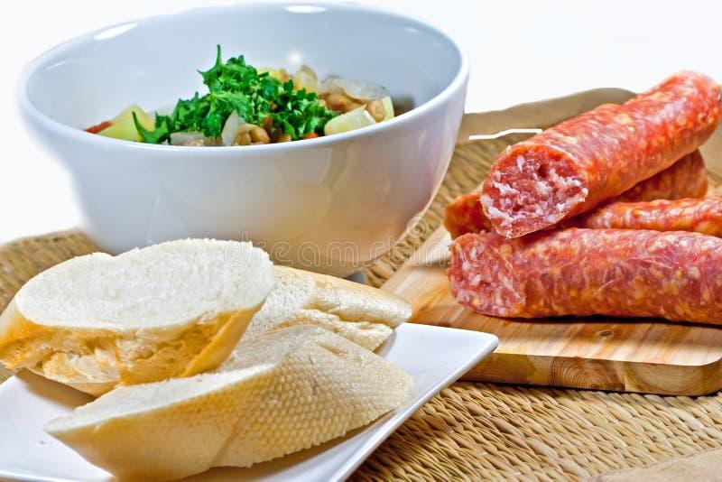 Soupe à lentille faite maison dans une cuvette, un mettwurst et un pain blancs avec le fond brun photographie stock