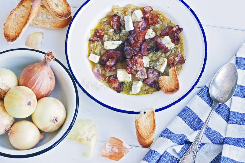 Soupe à oignon avec le lard et le camembert dans une plaque de métal blanche photo libre de droits
