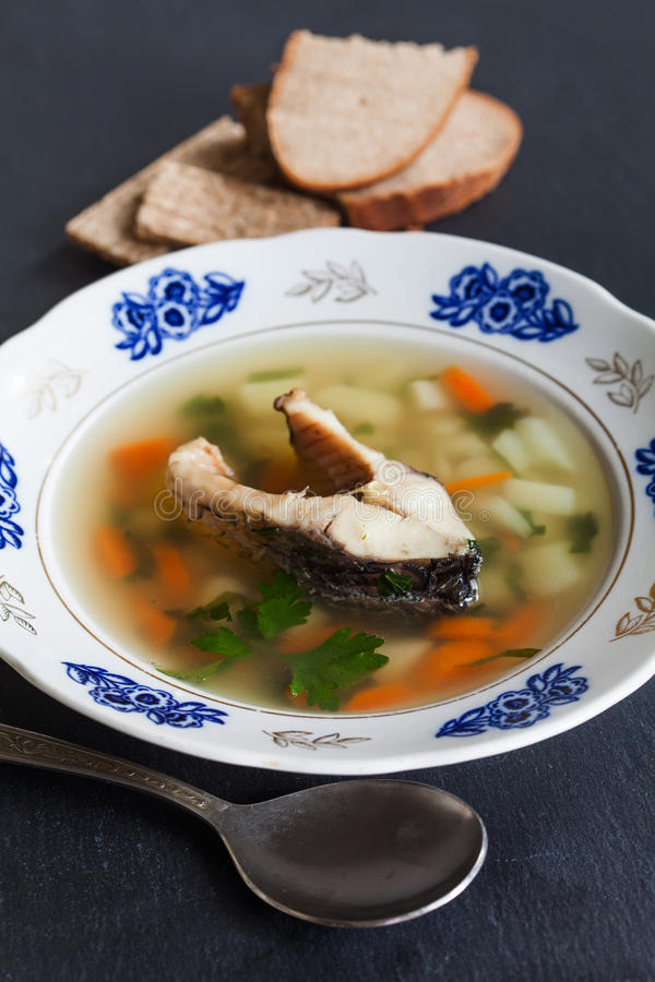 Soupe à poissons sur le fond en pierre noir Plat de vintage avec du pain coupé en tranches de carpe, de pomme de terre, de carott photographie stock libre de droits