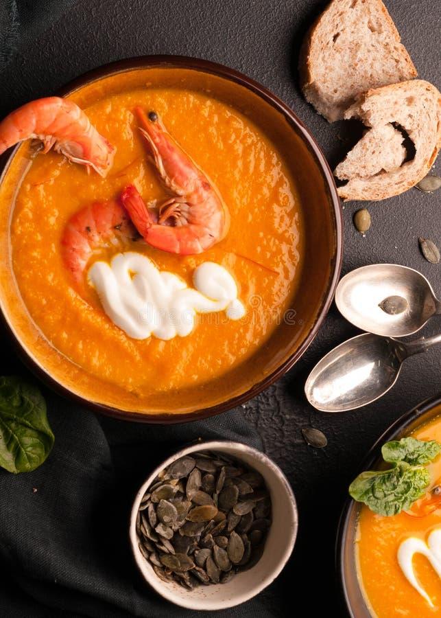 Soupe à potiron avec des crevettes, des graines de citrouille dans des cuvettes foncées et des cuillères d'argent photo stock