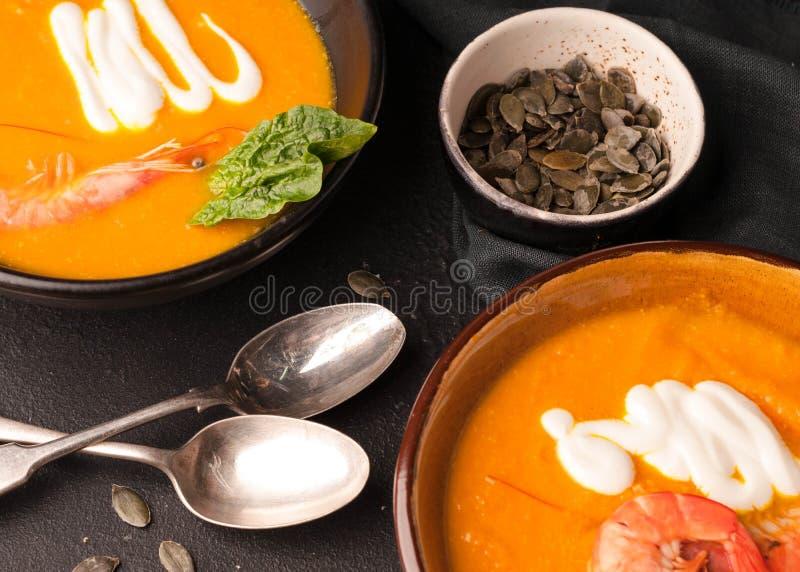 Soupe à potiron avec les crevettes, graines de citrouille dans des cuvettes foncées photo libre de droits