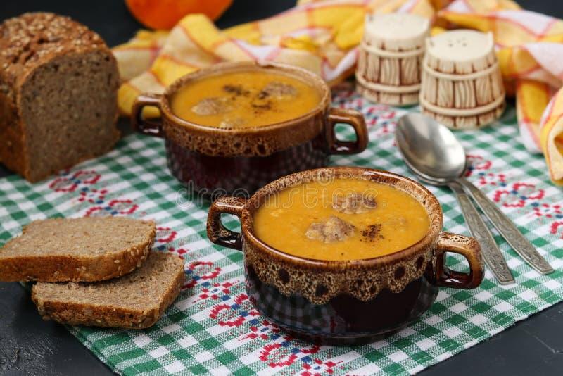 Soupe à potiron dans des cuvettes sur la serviette à carreaux sur un fond foncé photo stock