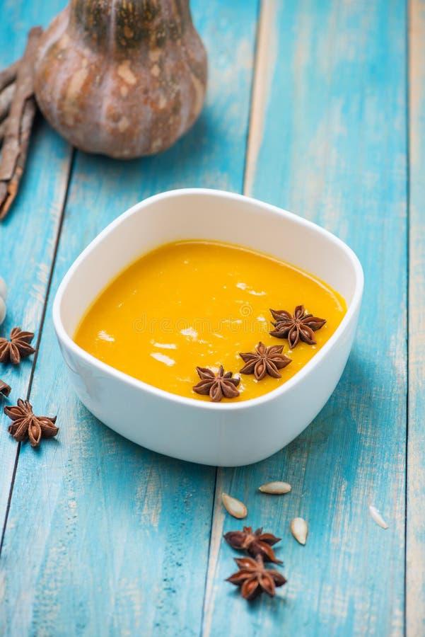 Soupe à potiron et à carotte avec de la crème et le persil sur b en bois bleu images libres de droits