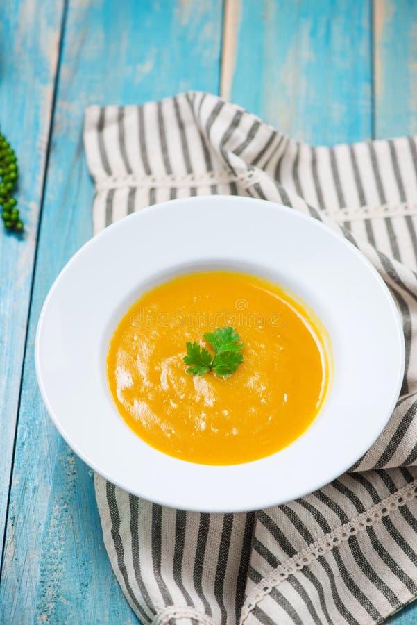 Soupe à potiron et à carotte avec de la crème et le persil sur b en bois bleu photographie stock