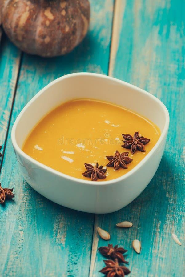 Soupe à potiron et à carotte avec de la crème et le persil sur le fond en bois bleu photos libres de droits
