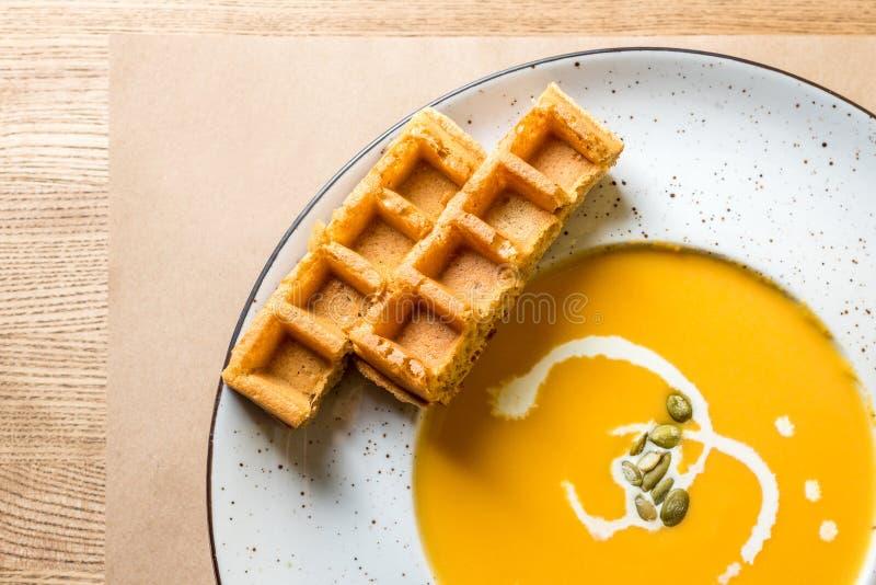 Soupe à potiron et à carotte avec les gaufres crèmes et belges sur le fond en bois rustique Configuration plate avec l'espace vid photographie stock