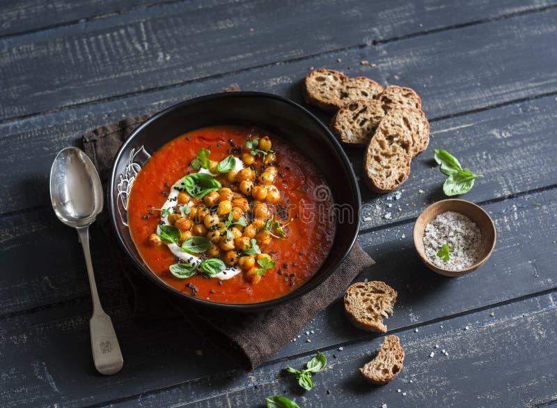 Soupe à tomate avec les pois chiches frits épicés sur une table en bois foncée, vue supérieure images libres de droits