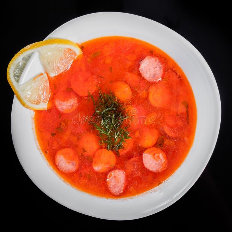 Soupe à tomate avec les saucisses fumées et les herbes dans la cuvette, d'isolement sur le fond noir, nourriture saine photos libres de droits