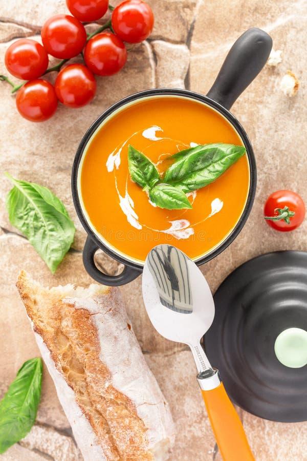 Soupe à tomate dans une cocotte en terre noire photos libres de droits