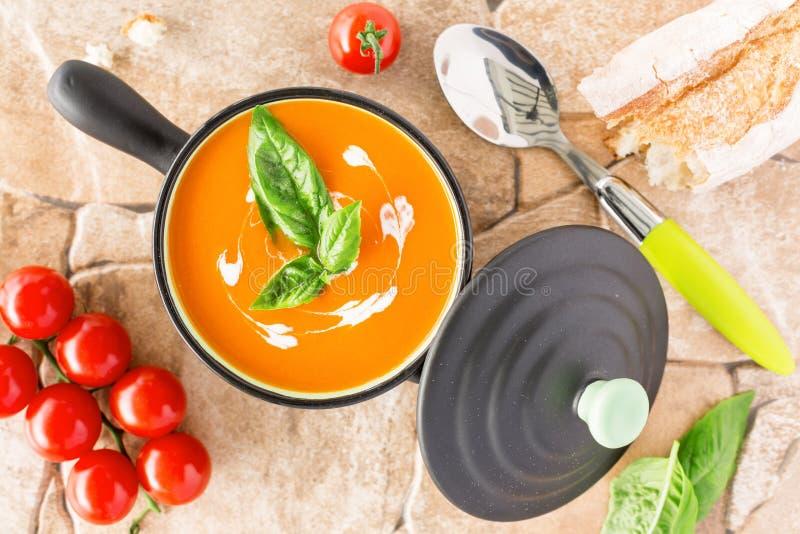 Soupe à tomate dans une cocotte en terre noire, bruinée avec de la crème photographie stock libre de droits