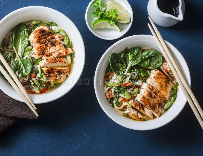Soupe asiatique à style de poulet, de nouilles et de légumes sur un fond bleu image libre de droits