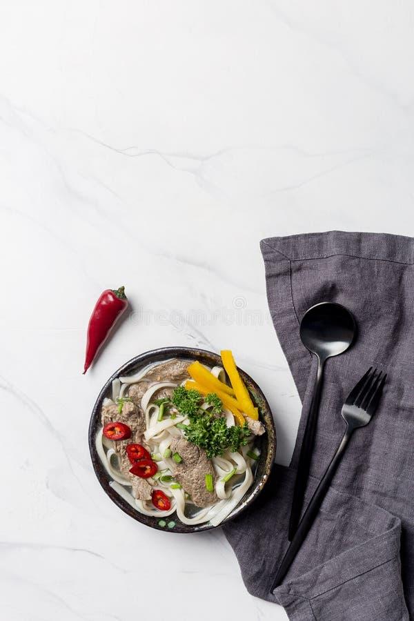 Soupe asiatique avec la nouille, le boeuf et les légumes dans la cuvette avec la serviette sur le fond blanc photos libres de droits