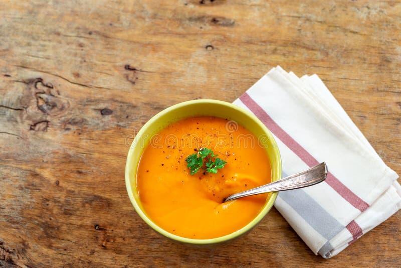Soupe au curry à carotte avec de la crème et table en bois naturelle d'herbes fraîches la vieille photos libres de droits