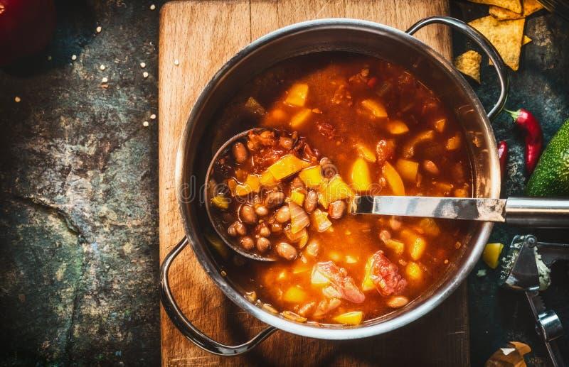 Soupe aux fèves végétarienne en faisant cuire le pot avec la poche sur le fond rustique foncé, vue supérieure, fin, endroit pour  photographie stock libre de droits