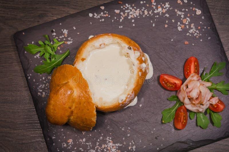 Soupe aux pois fraîche dans un bol de pain, sur un conseil en bois avec du sel et le papper images libres de droits
