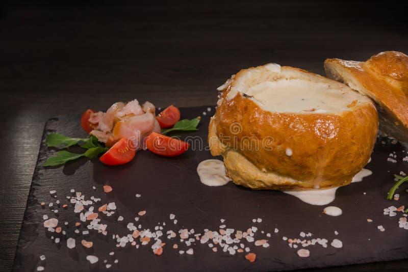 Soupe aux pois fraîche dans un bol de pain, sur un conseil en bois avec du sel et le papper photographie stock libre de droits