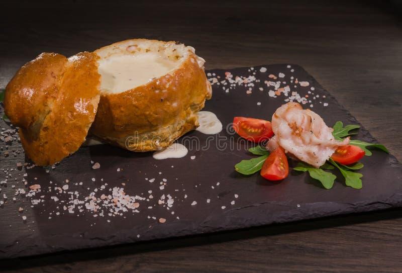 Soupe aux pois fraîche dans un bol de pain, sur un conseil en bois avec du sel et le poivre photographie stock libre de droits