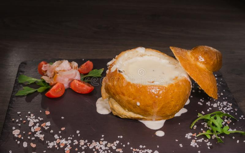 Soupe aux pois fraîche dans un bol de pain, sur un conseil en bois avec du sel et le poivre photos libres de droits