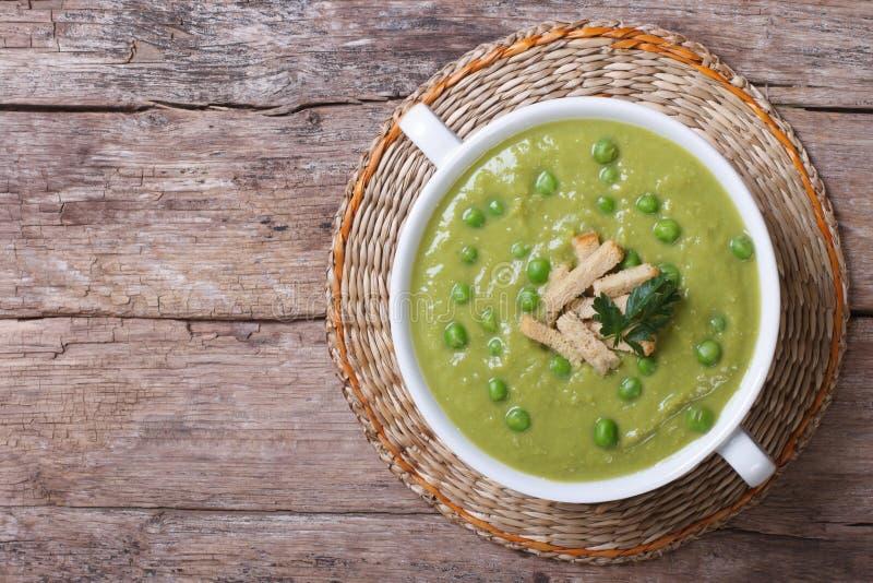 Soupe aux pois verte avec des croûtons sur la vieille table photos stock