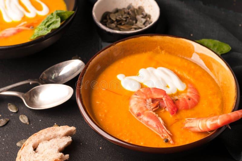 Soupe avec des crevettes, des graines de citrouille dans des cuvettes foncées et des cuillères d'argent image stock