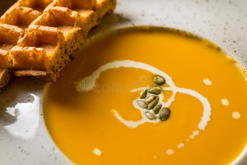 Soupe chaude à potiron dans la cuvette blanche avec les gaufres belges Vue d'en haut, macro vue images libres de droits