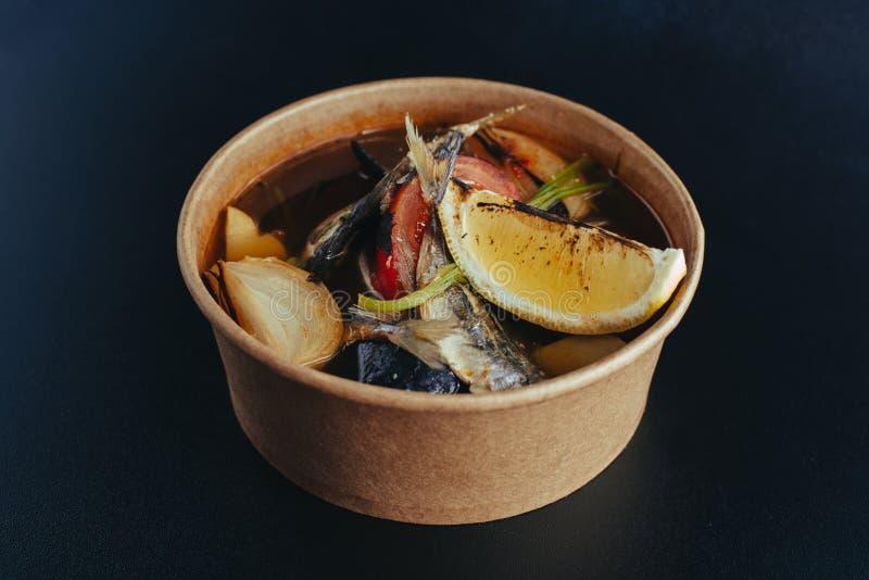 Soupe chaude fraîche à poissons avec des ingrédients et des épices pour faire cuire sur le fond foncé Nourriture de rue image stock