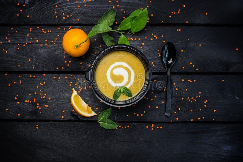Soupe crème à lentille avec la cuillère et le citron noirs sur le fond en bois foncé Image de vue supérieure photographie stock