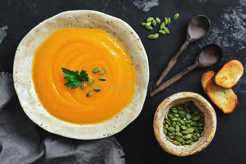 Soupe crème à potiron avec des graines et pain grillé dans une cuvette rustique en céramique sur un fond en pierre foncé Soupe de photographie stock