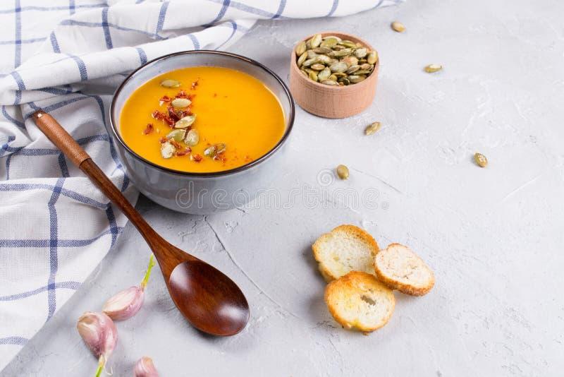 Soupe crème à potiron avec les graines, le pain grillé et l'assaisonnement dans une cuvette en céramique sur une table image libre de droits