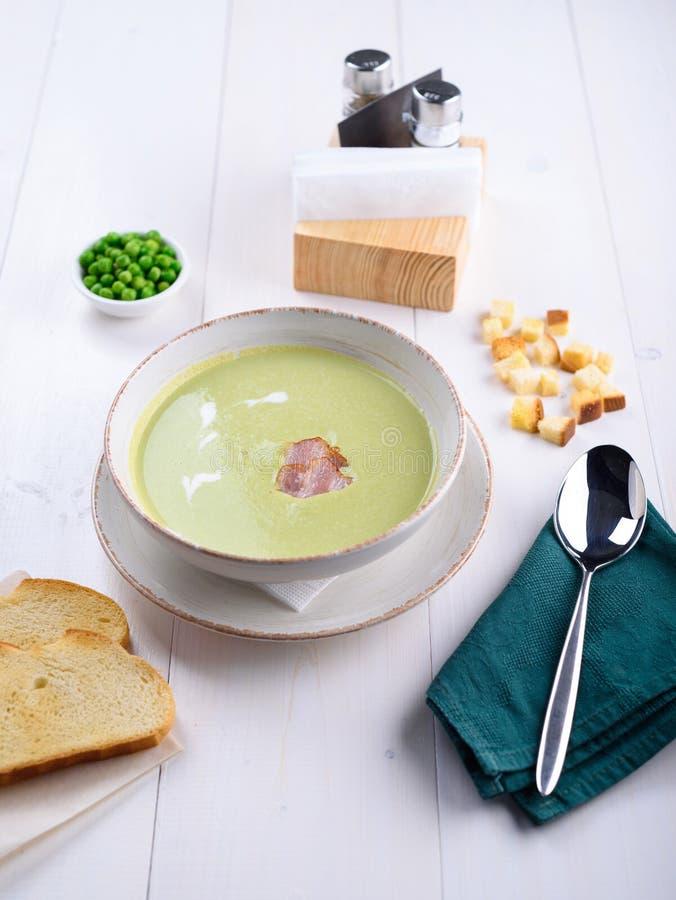 Soupe crème aux pois avec le lard dans un plat blanc avec du pain grillé photos stock