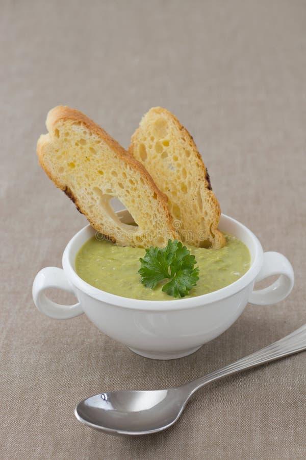 Soupe crème aux pois avec le persil et les croûtons photographie stock