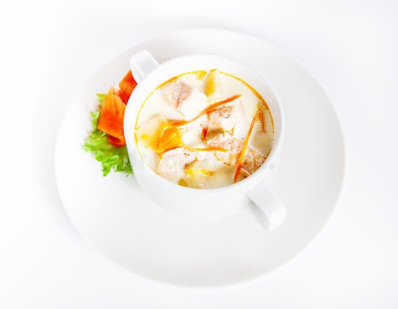 Soupe crémeuse délicieuse avec des saumons sur le blanc photos stock
