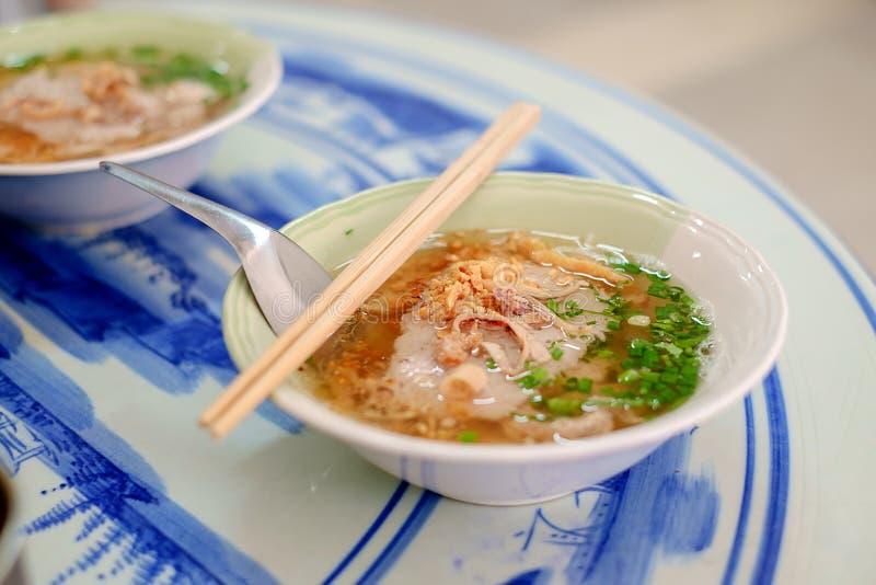 Soupe de nouilles asiatique de porc dans une cuvette avec la cuillère courte et le cho en bois photos stock