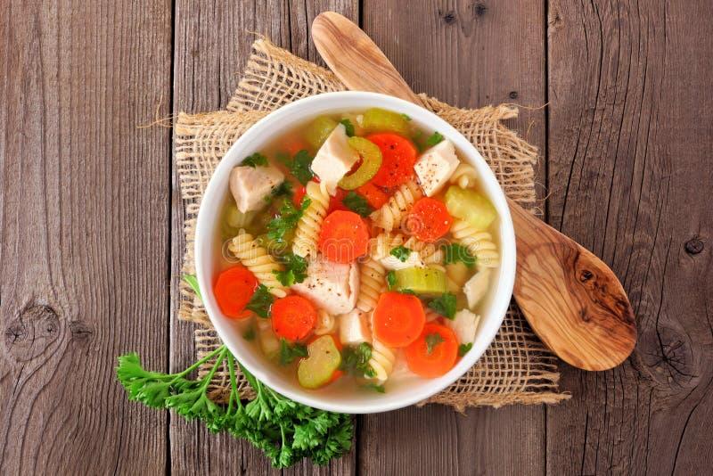 Soupe de nouilles faite maison de poulet avec des légumes, vue supérieure sur un fond en bois image libre de droits