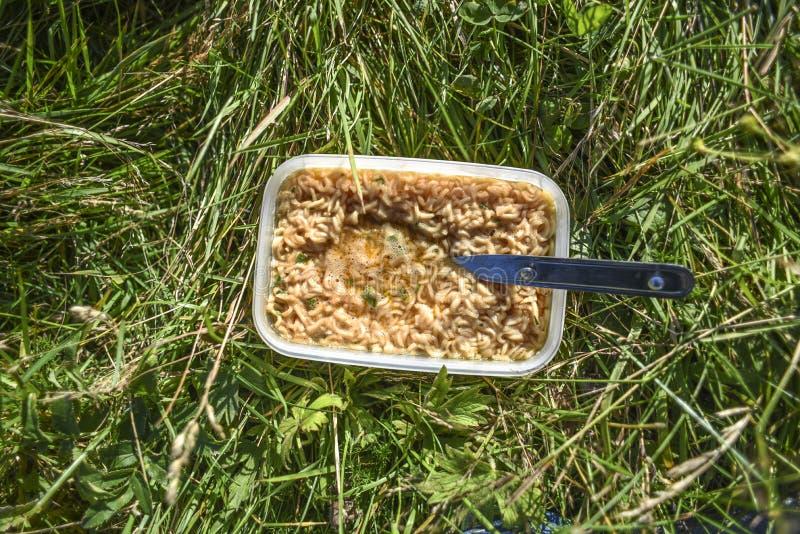 Soupe de nouilles instantanée se trouvant sur l'herbe tout préparée photos libres de droits