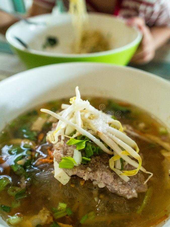Soupe de nouilles de vermicellis avec du porc et des légumes dans r traditionnel photographie stock