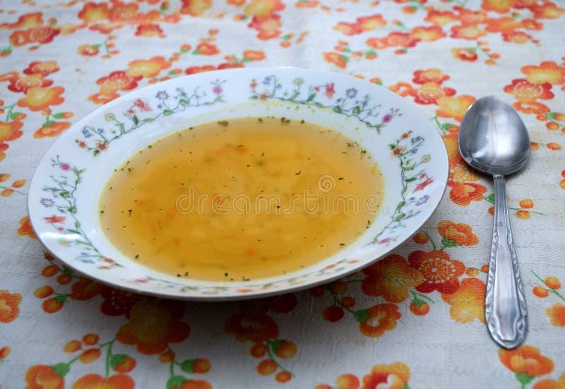 Soupe domestique avec des nouilles dans un plat décoré des fleurs image stock