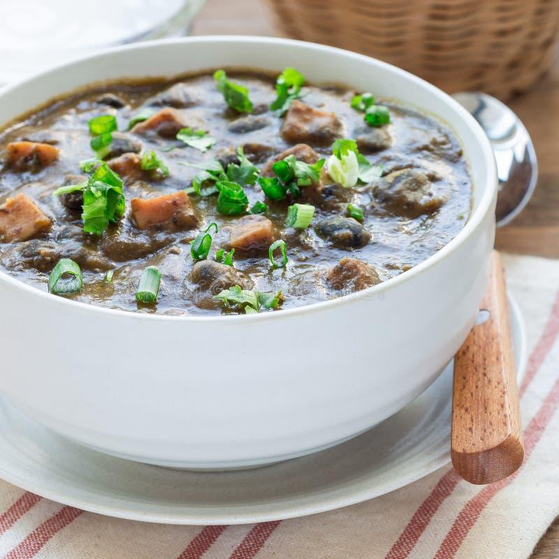 Soupe faite maison à haricot noir et à jambon dans la cuvette en céramique sur la table en bois, format carré photos stock