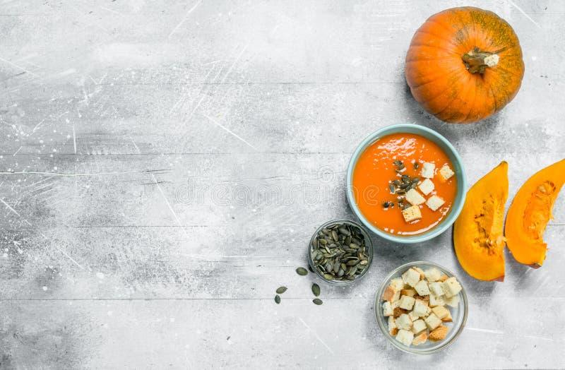 Soupe, graines et biscottes à potiron dans des cuvettes photographie stock