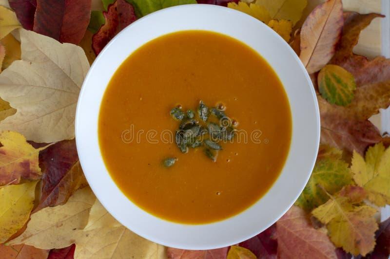 Soupe orange lumineuse à potiron savoureux avec les graines vertes servies du plat blanc et des feuilles colorées automnales photo libre de droits