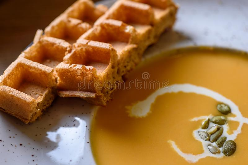 Soupe rôtie à potiron et à carotte avec de la crème, les graines de citrouille et la gaufre belge sur le fond en bois de table photo libre de droits