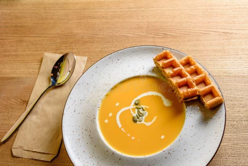 Soupe rôtie à potiron et à carotte avec de la crème, les graines de citrouille et la gaufre belge sur le fond en bois de table photographie stock