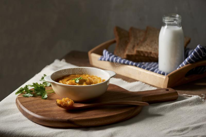 Soupe rôtie à potiron et à carotte avec de la crème et pain grillé sur le fond en bois Copiez l'espace photographie stock libre de droits
